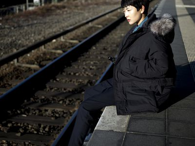 woman sitting on train platform with her legs hanging over the edge