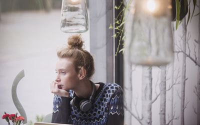 young woman with headphones around her neck and chin resting on hand, looking out cafe window