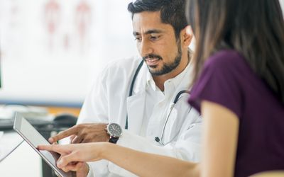 doctor and patient pointing to tablet