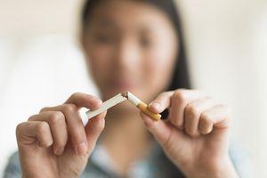 Woman breaking cigarette in half, quitting smoking.