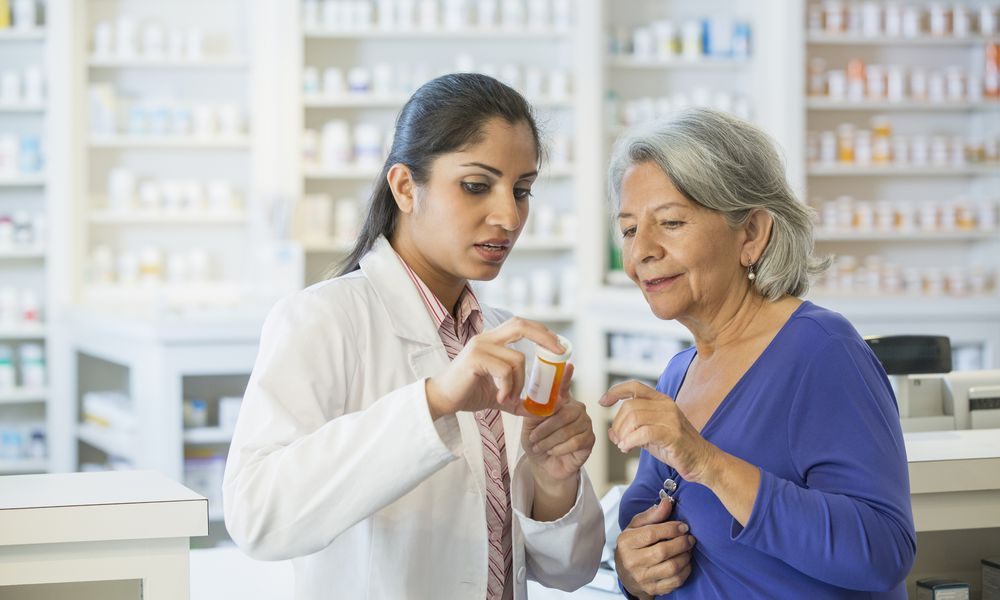 Pharmacist talking to woman about medication