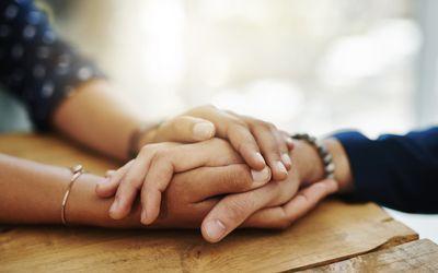 holding hands in comfort.