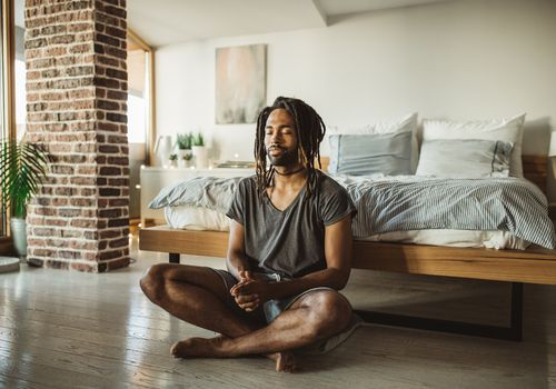 Man sitting and meditating at the end of his bed