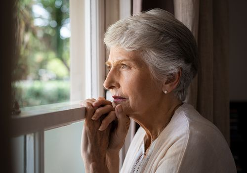 Old woman staring blankly outside.