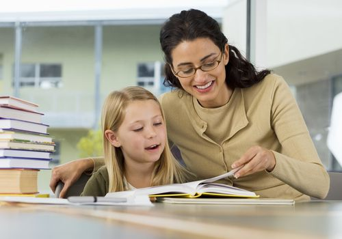 woman helping child read book