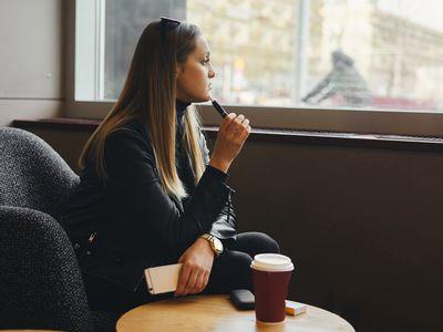 woman looking pensive holding vape pen
