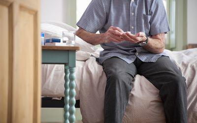 Older man taking pills on bed
