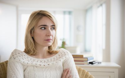 Lonely Caucasian woman sitting in living room