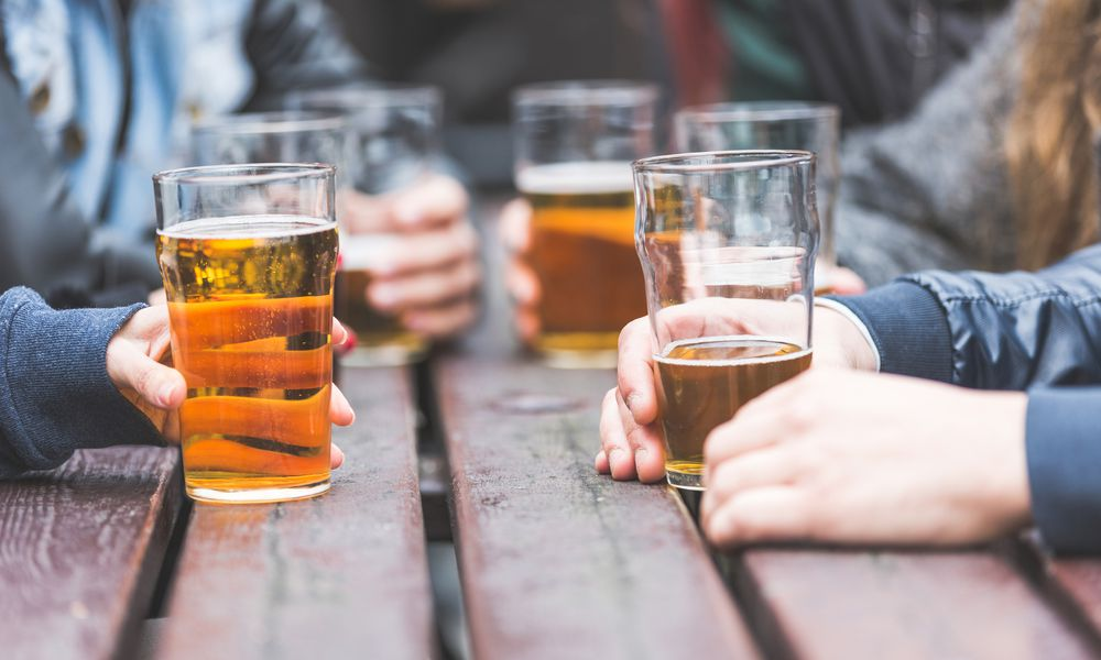 close-up of hands holding beers
