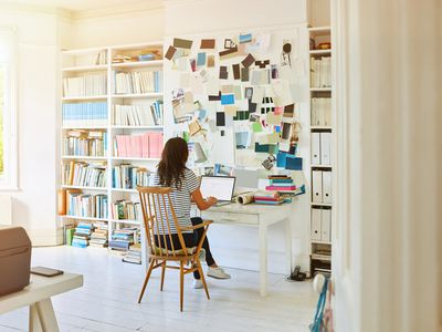 Woman sitting at desk working in home office.