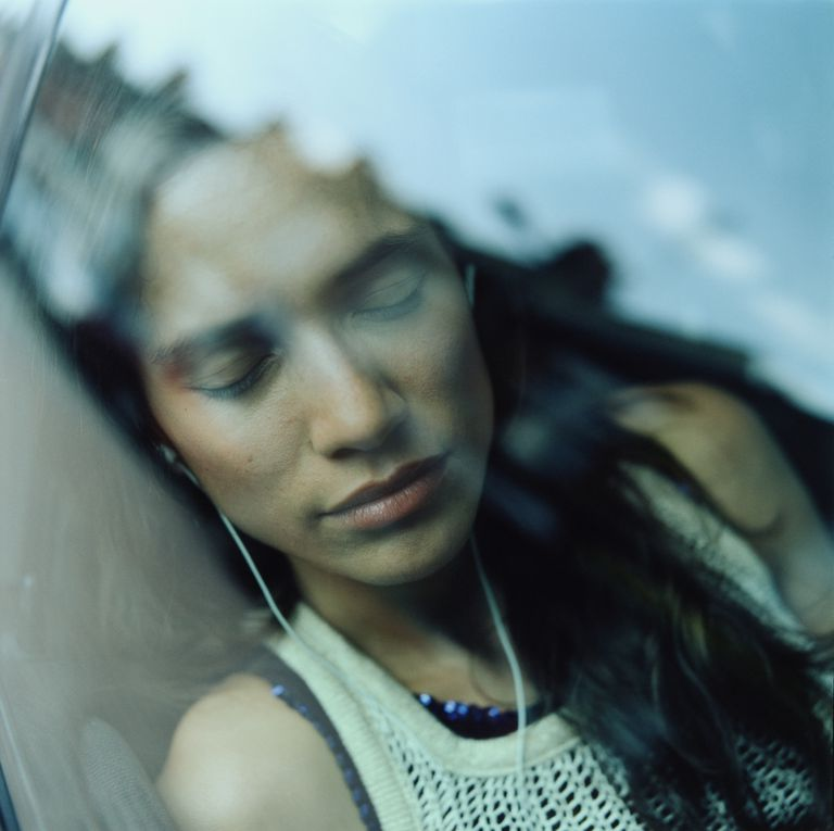 Young woman in car, sleeping against window, close-up