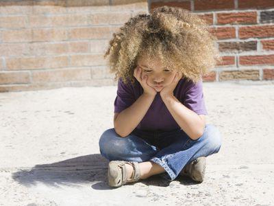 Sad, mixed race boy sitting on sidewalk