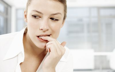 Anxious woman chewing on her fingernail