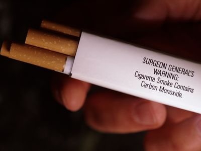 man't hand holding cigarette carton with warning