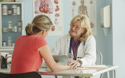 woman talking to female doctor in office