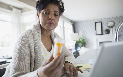 Woman reading prescription bottle label at laptop