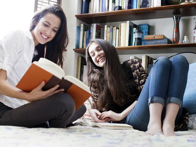 Two Girl Friends Reading In Bed And Laughing
