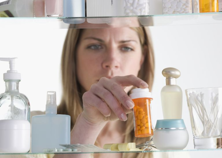 Woman Taking Pill Bottle Out of Cabinet