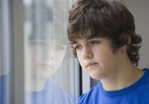 Teenaged boy looking out window