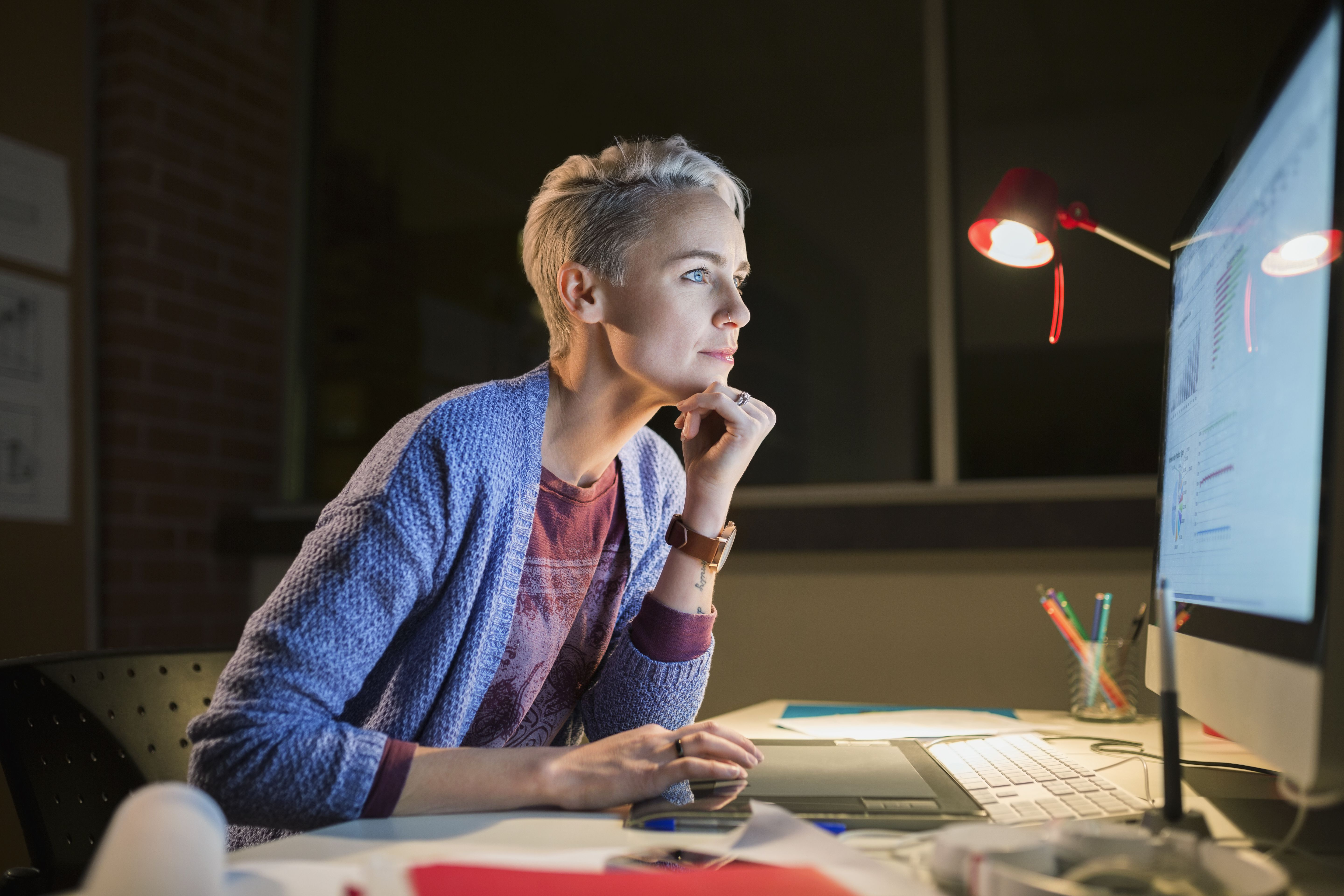 Woman using computer in office at night