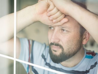 Man looking sad while looking out the window.