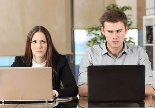 Upset woman and man sitting side by side working on laptops