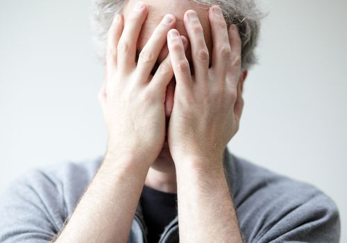 Distressed man with his hands covering his face