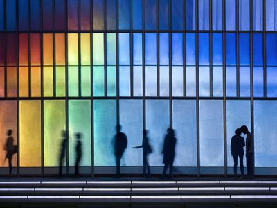 People passing colorful LED illuminated facade