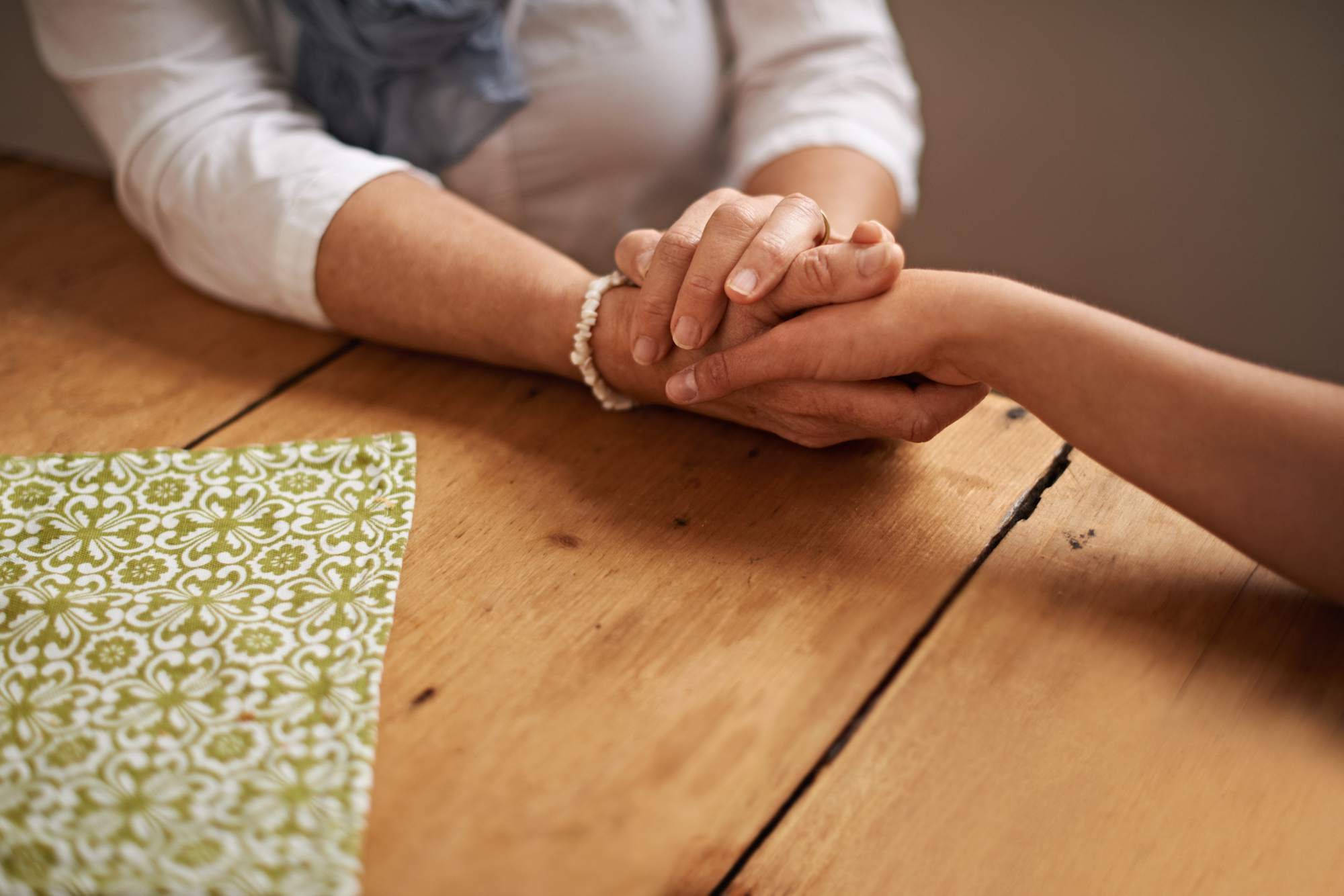 women holding hands on table