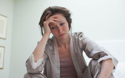 Depressed woman in pajamas sitting in bed