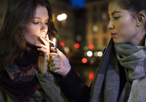 Young woman lighting a joint for her friend