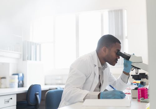 Scientist at a microscope writing down research.