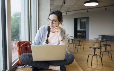 Female university student using laptop, looking out window in student lounge