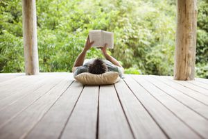 man lying on a deck reading a book