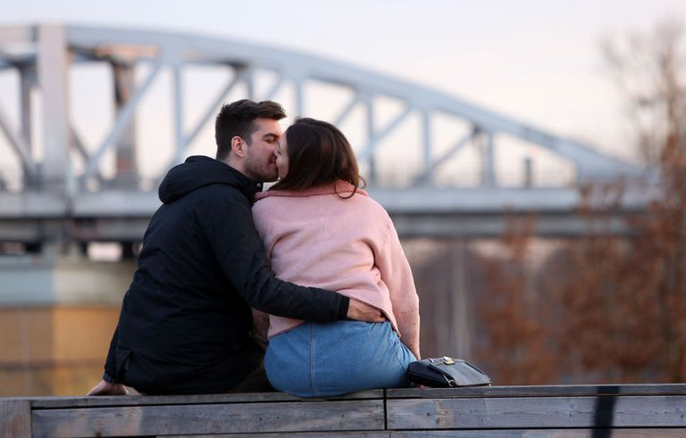 Couple embracing on a bench.