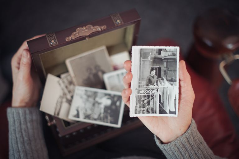 Woman holding black and white photos from a suitcase.