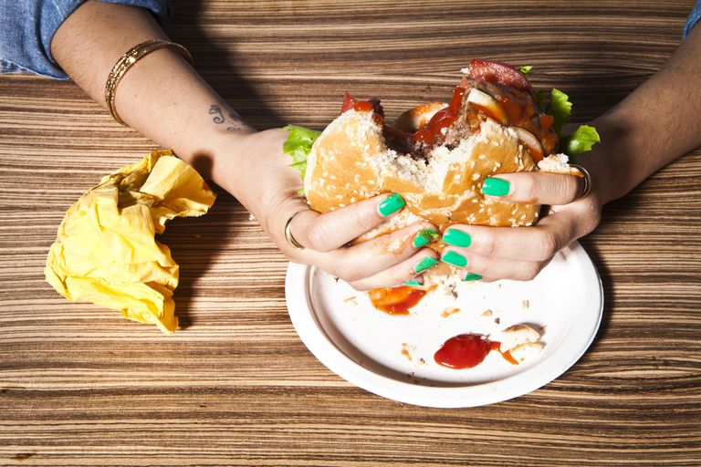 Stress And Weight Gain How Can Stress Make You Overweight Closeup Of Woman Holding Hamburger