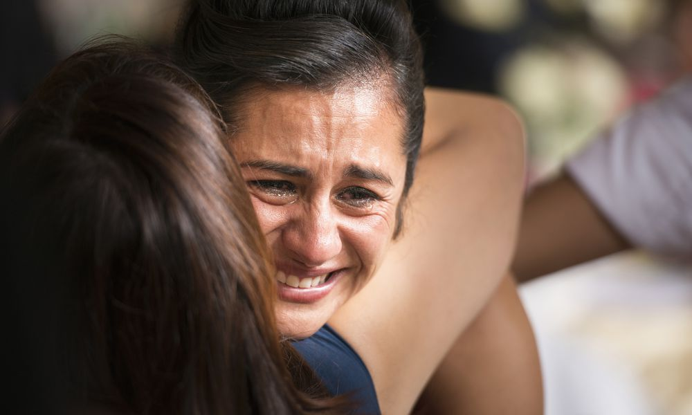 Woman crying with other woman hugging him.