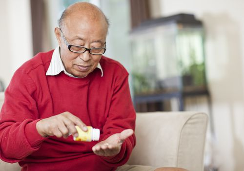 senior asian man taking medication
