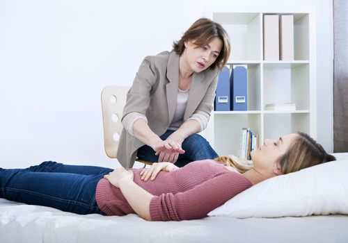 Therapist performing hypnotherapy on a woman lying down
