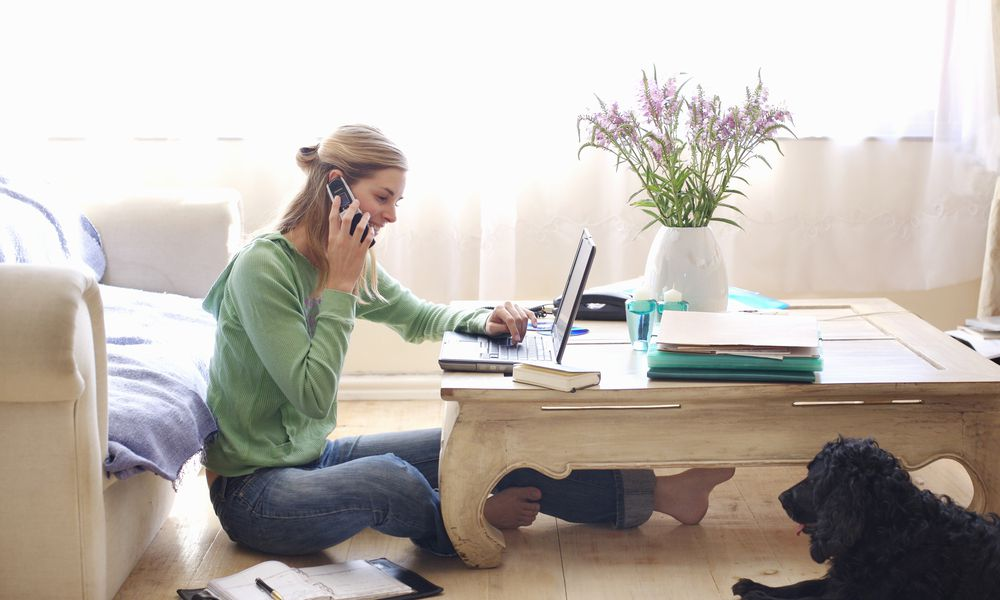 Woman working at laptop in living room on the phone