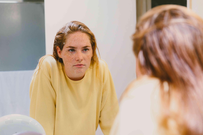 Depressed Teen Looks At Herself in Bathroom Mirror
