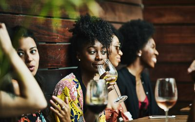A woman slowly sips a glass of wine at a restaurant, surrounded by happy friends.