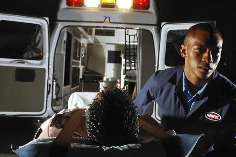 a paramedic rushing a patient to the ambulance
