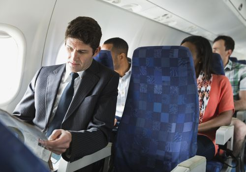 Businessman reading newspaper in airplane