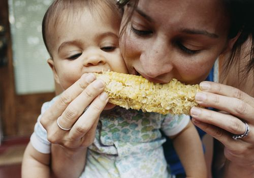 mother and baby eat corn on the cob