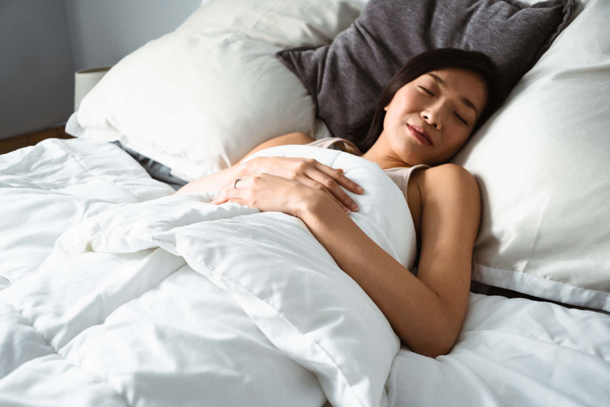 Woman lying in bed with eyes closed.