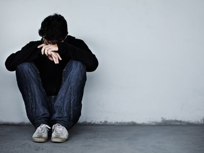 upset young man sitting against wall with head on hands