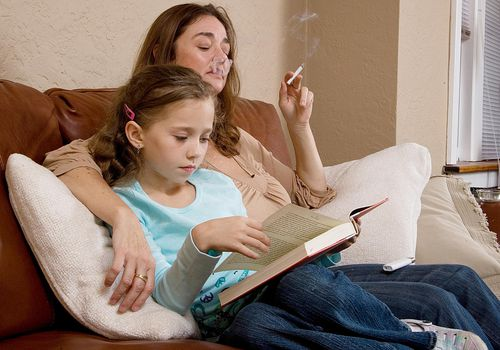 Mom smoking next to reading daughter on a couch