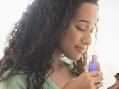 woman smelling aromatherapy oil bottle